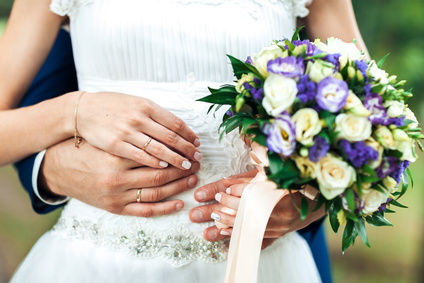 closeup, hands of bride and groom with wedding rings and bouquet